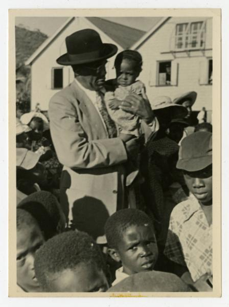 Bishop Dougal Ormonde Beaconfield Walker holding a toddler and surrounded by a group of unidentified individuals while visiting St. Vincent in the West Indies.