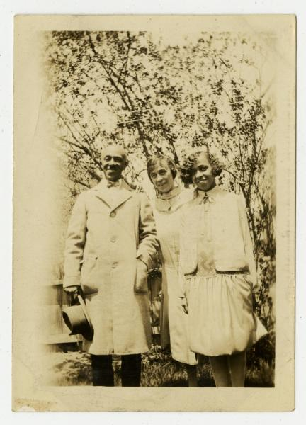 Eva Walker, the mother of Yvonne Walker-Taylor standing with two unidentified individuals.