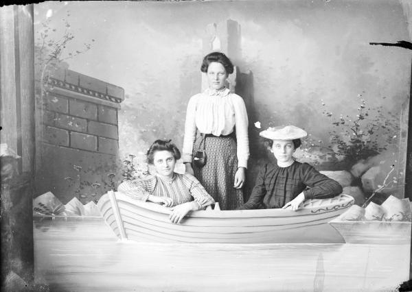 Women seated in prop boat photograph