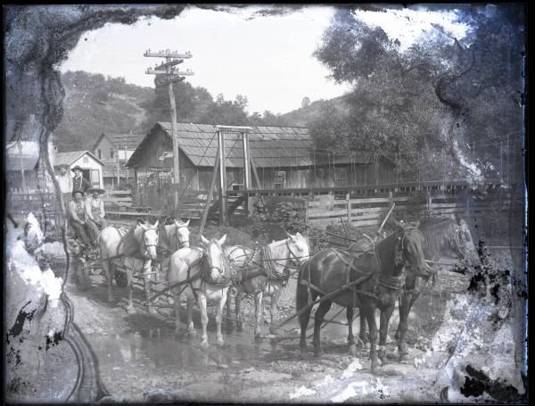 Six-in-hand horse-drawn cart with workers