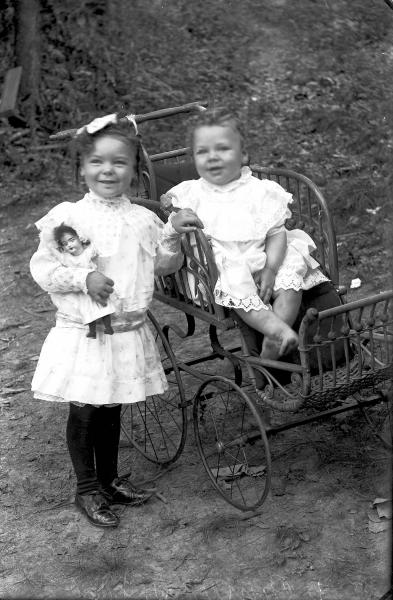 Child in perambulator and girl with doll