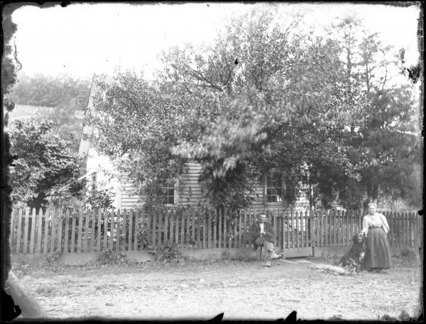 Couple and dog in front of home