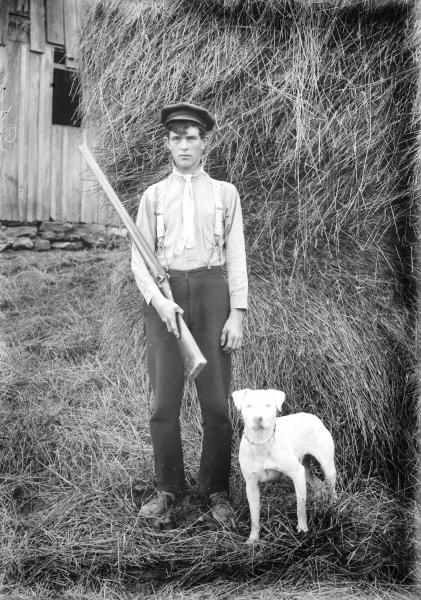 Young man with shotgun and dog