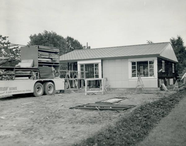 Lustron house under construction with Lustron truck