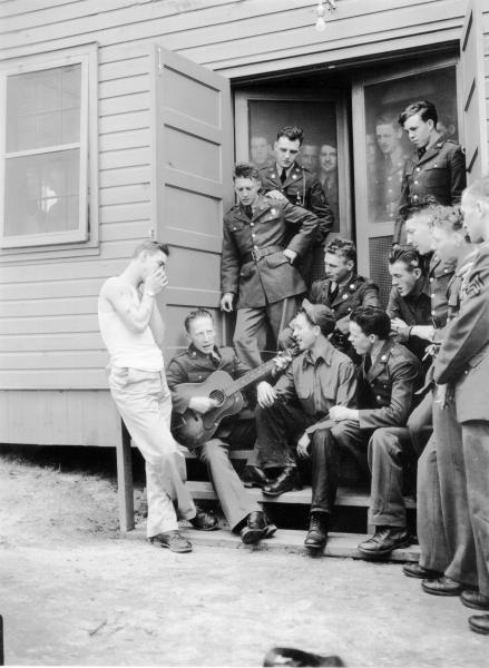 Soldier playing guitar in front of barracks photograph
