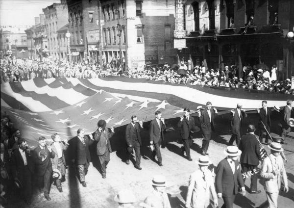 Men carrying large American flag
