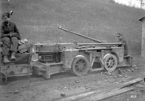 Young mine runners with Jeffrey mining machine photograph