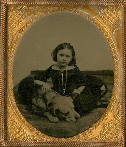 Young girl with dog posing in photograph