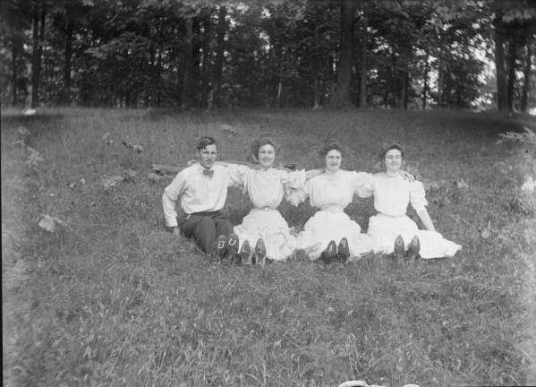 Four people sitting on grass photograph