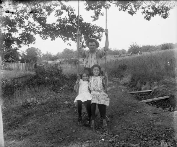Girls on swing with father