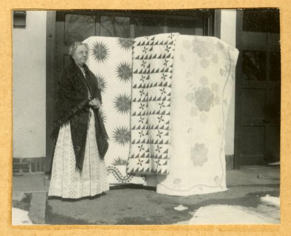 Mrs. McCall with antique quilts
