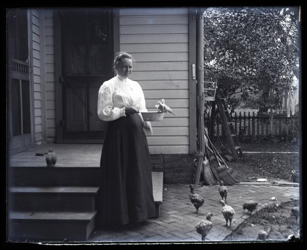 Mrs. Kinley and doves at back of house