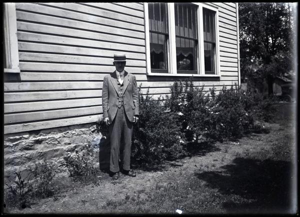 Harry Kinley standing along outside of house