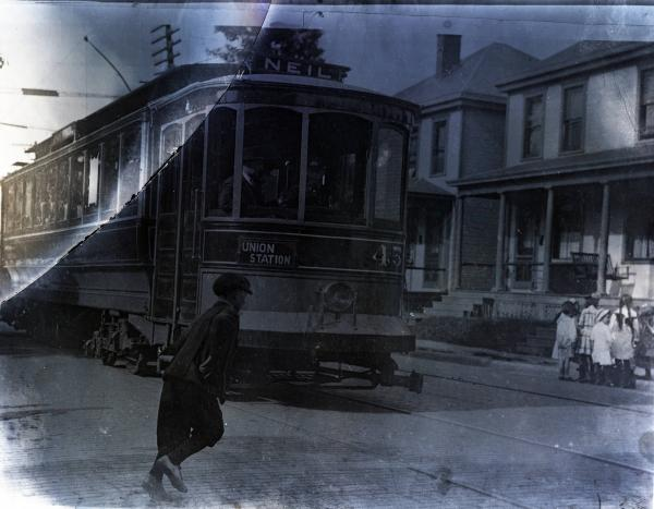 Boy running in front of moving streetcar