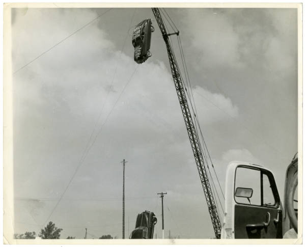 Car suspended from crane