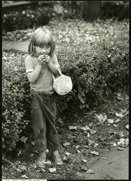 Young girl standing by hedge