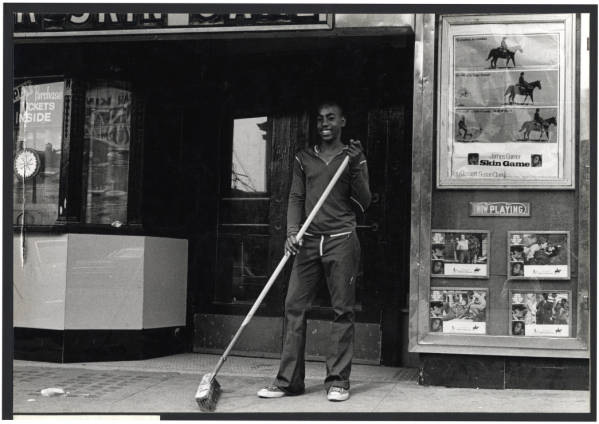 Young man sweeping sidewalk at Garden Theater