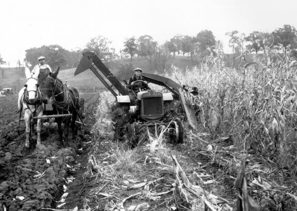 Tractor towing corn-picker in field photograph