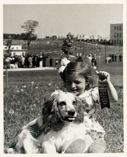 Girl and dog with a special prize ribbon
