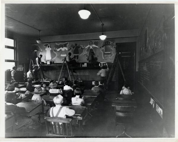 Artists painting murals in a classroom